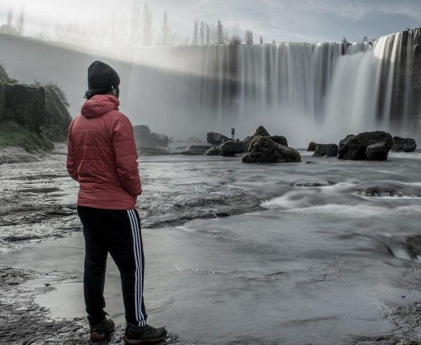 cascada con una persona mirando de casaca roja